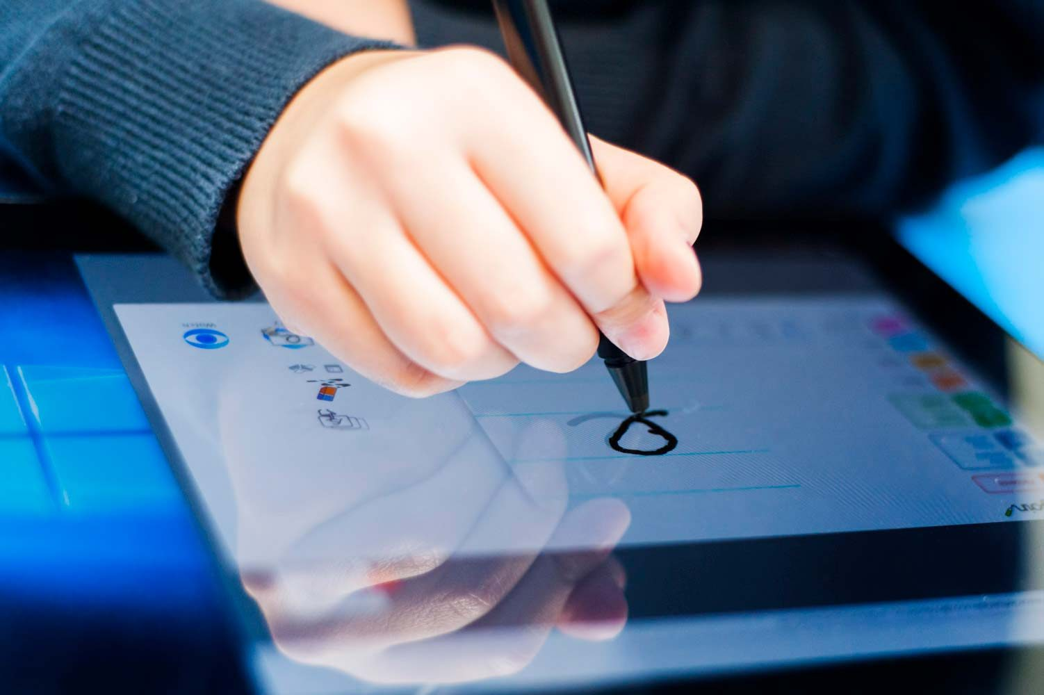 Close up photograph of school pupil drawing on an electronic tablet