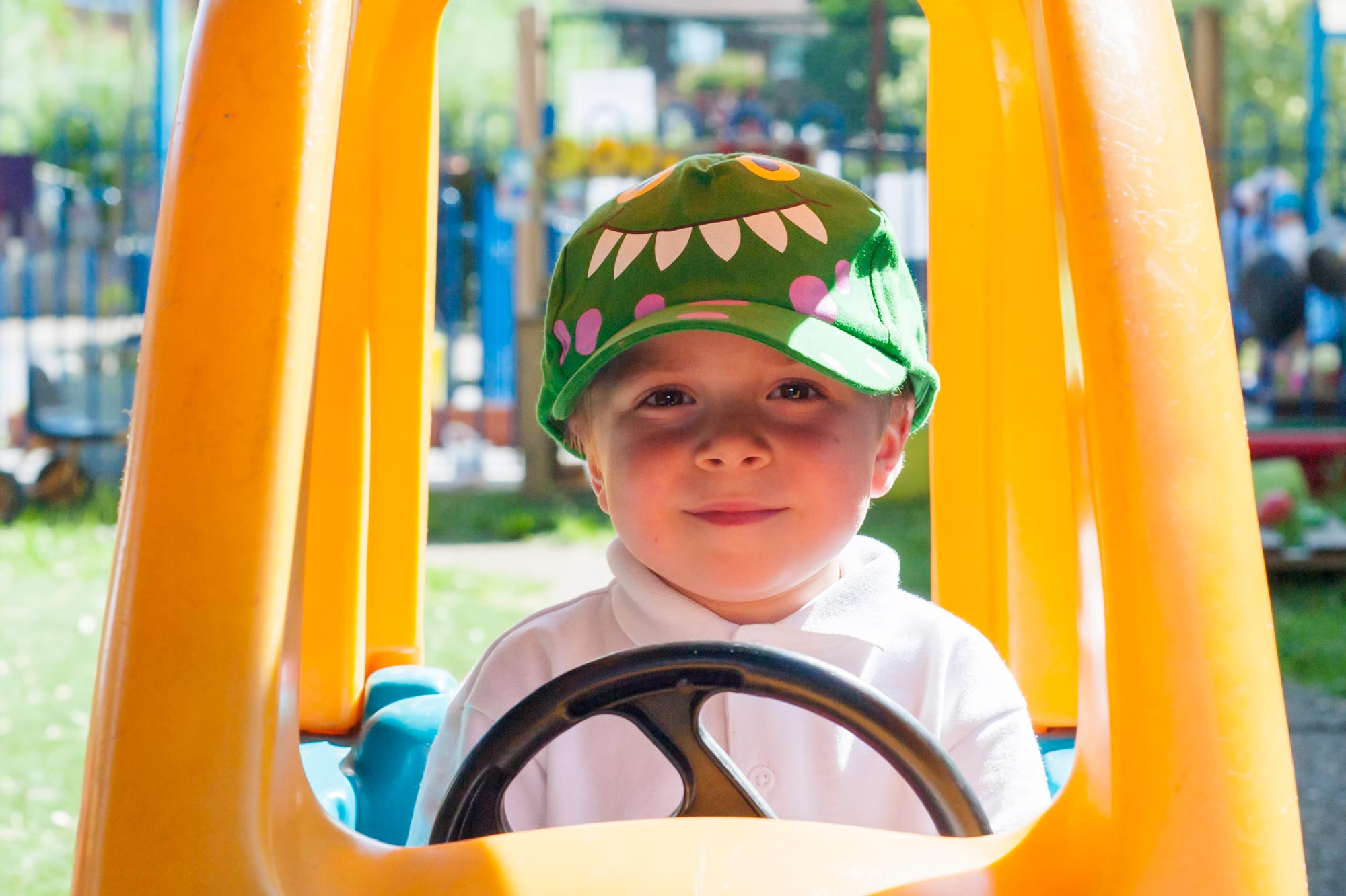 School child in a play car outdoors