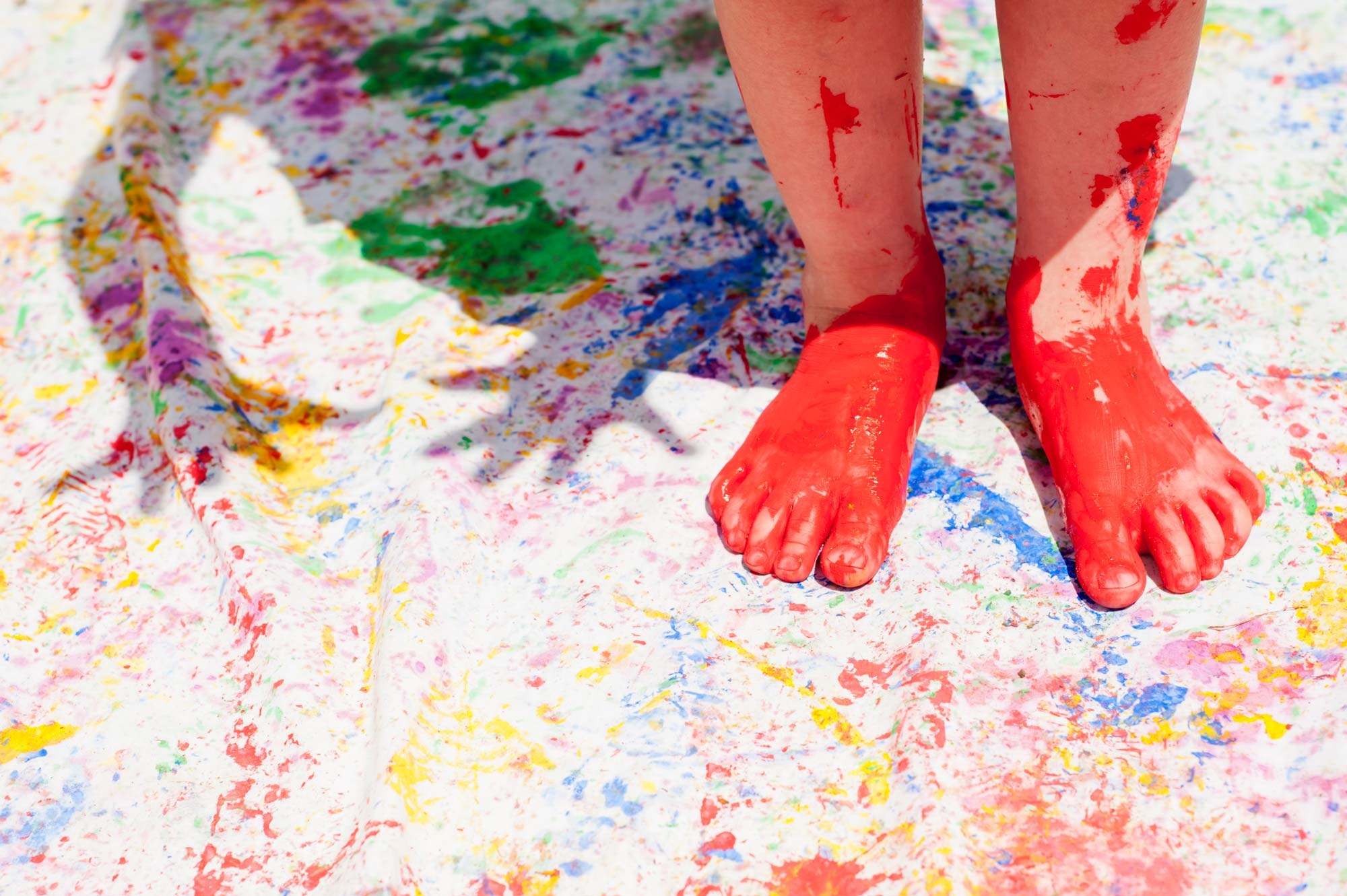 Child painting with feet outdoors