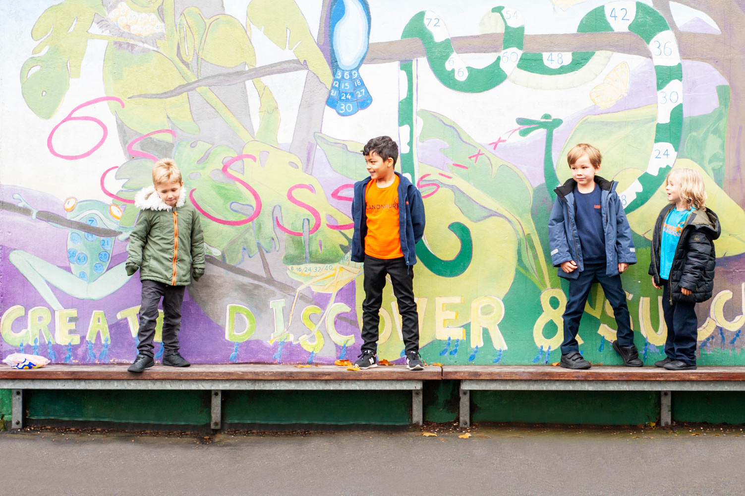 London school website photography of pupils standing in front of a painted wall