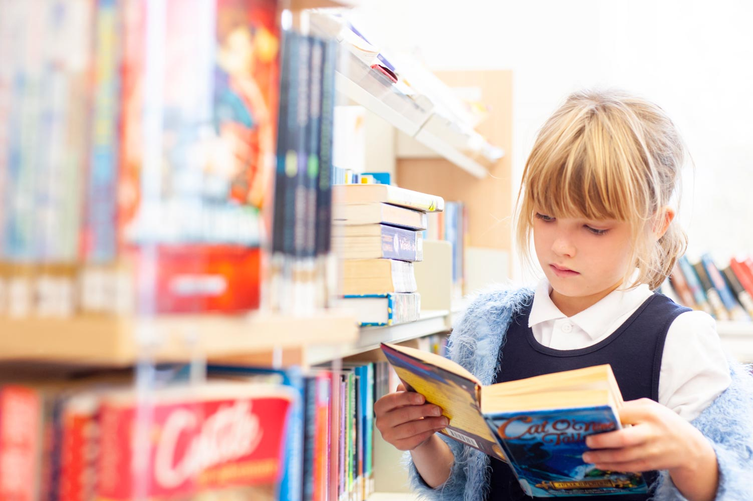 School pupil reading in the school library