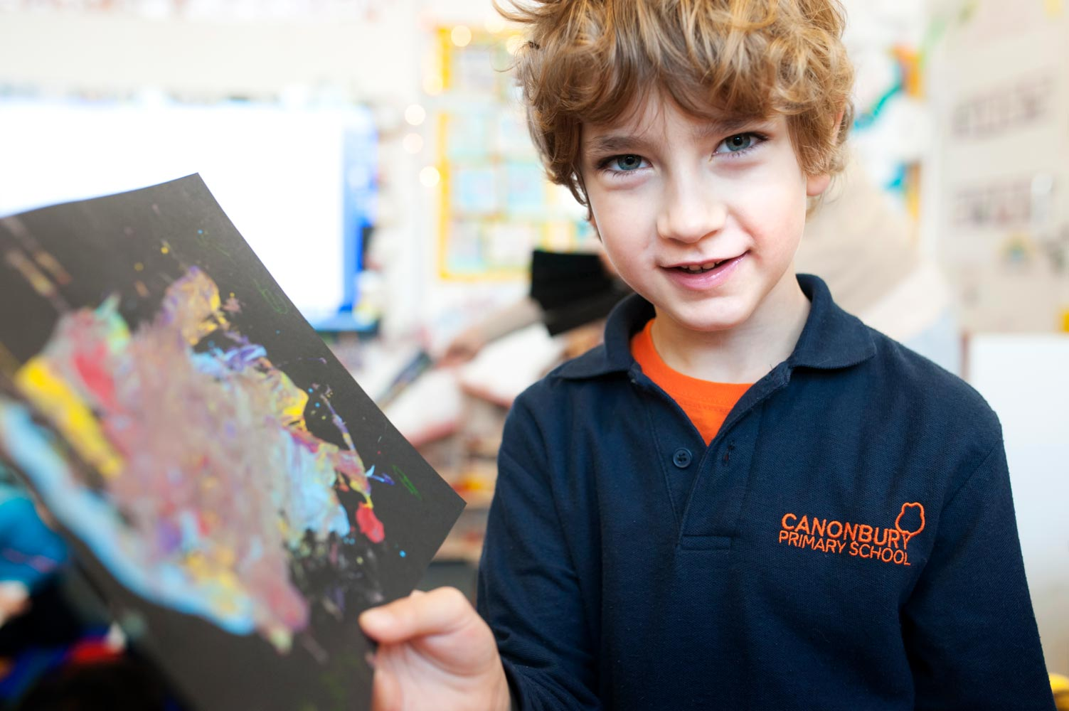 School pupil showing artwork to the camera