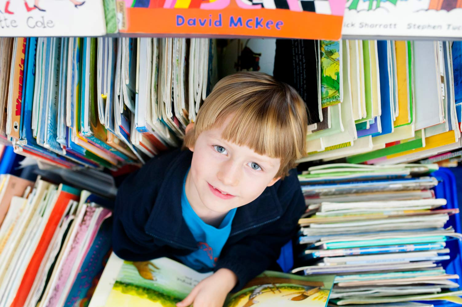 School pupil looking at the camera surrounded by books