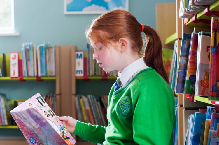 School pupil reading in library