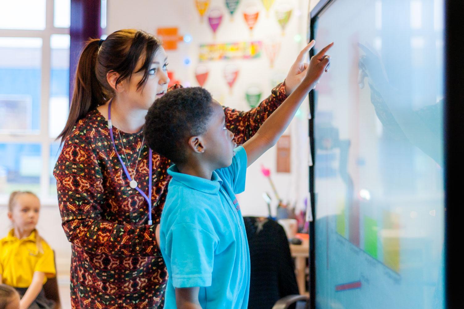 Pupil and teacher using classroom touchscreen