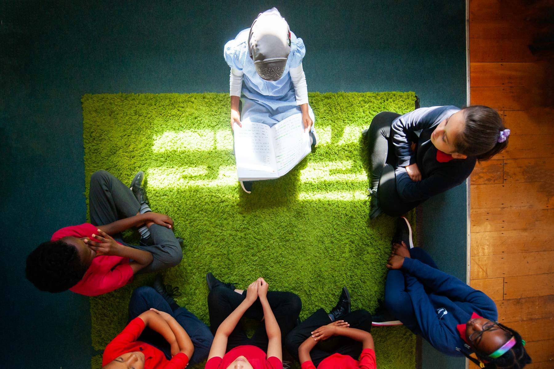 School pupil reading to peers