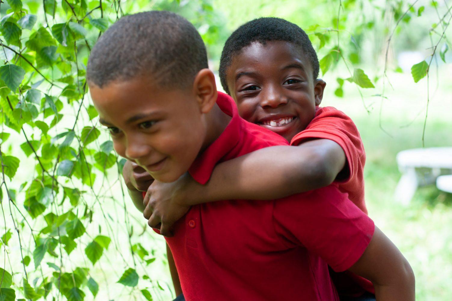 School pupils piggyback in garden