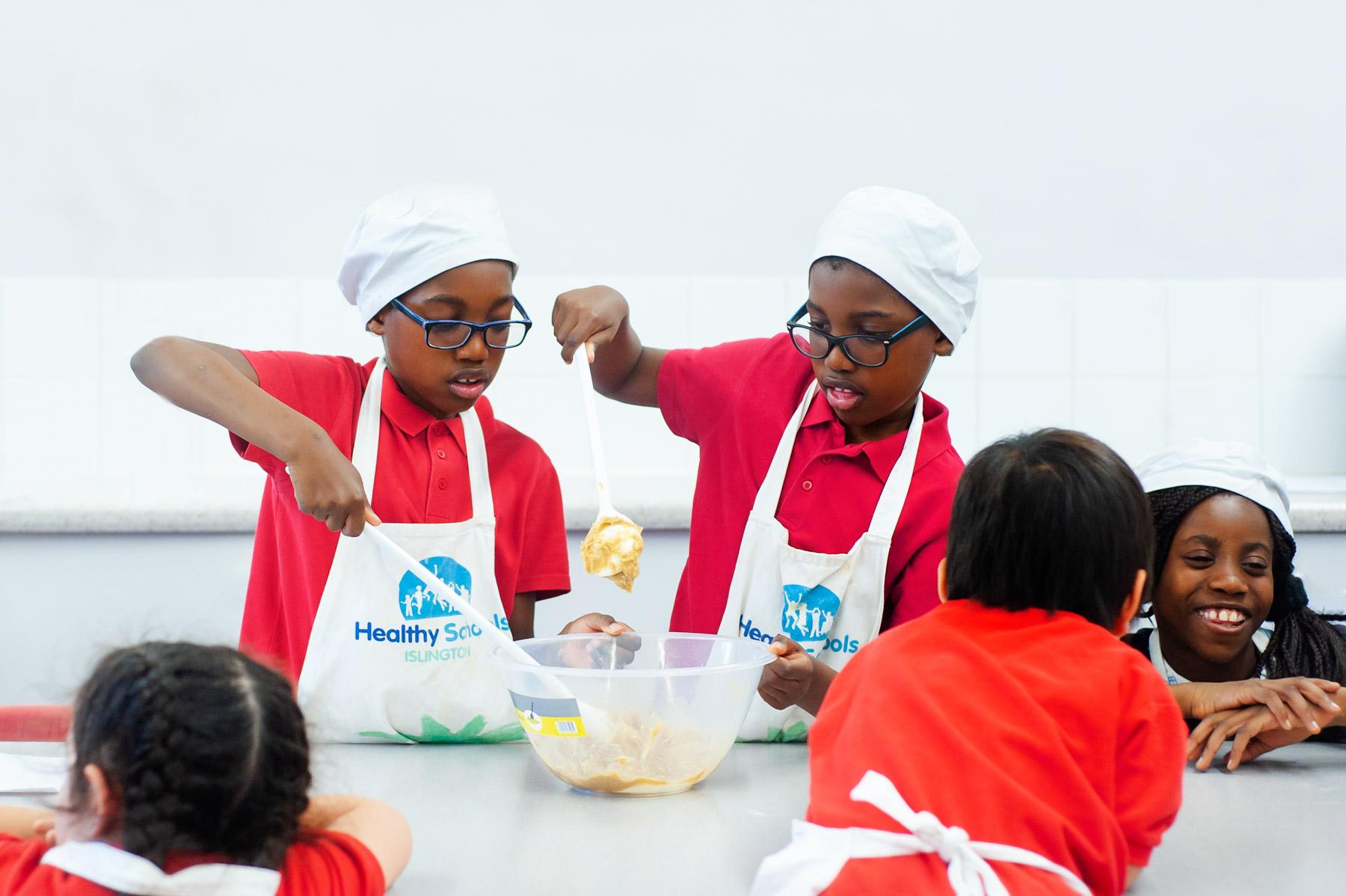 School pupils making a cake mix
